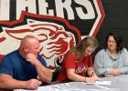 Concordia High School senior Katlynn Miller, middle, signs a basketball letter-of-intent with Bethel College on Monday. Also pictured are Miller's mother, Kathy, right, and father, Tony.